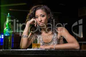 Depressed woman having whiskey at bar counter
