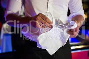 Barkeeper wiping a wine glass