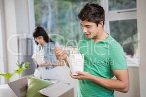 Young man and woman eating noodles at home