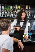 Barmaid pouring beer into beer glass for a man at bar counter