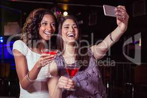 Young women taking a selfie while having a cocktail drink