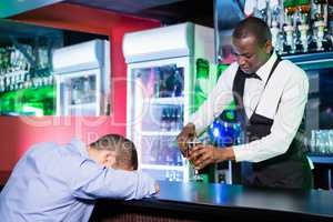 Drunk man sleeping with his head on bar counter