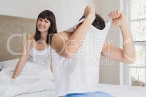Man removing his vest in front of woman