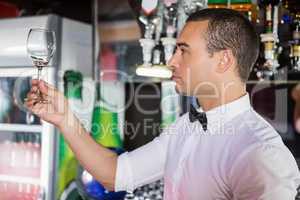 Barkeeper checking a wine glass