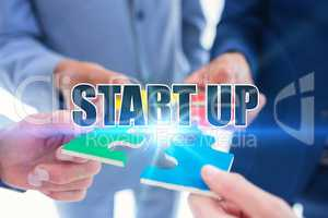 Start up against business colleagues holding piece of puzzle
