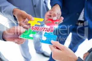 Solution against business colleagues holding piece of puzzle