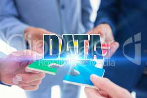 Data against business colleagues holding piece of puzzle