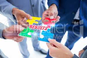 Results against business colleagues holding piece of puzzle