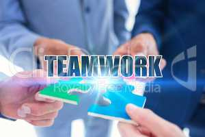 Teamwork against business colleagues holding piece of puzzle