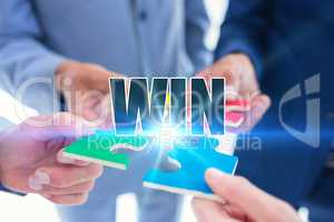 Win against business colleagues holding piece of puzzle