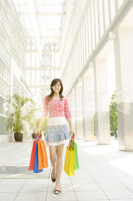 Asian woman walking out from shopping mall
