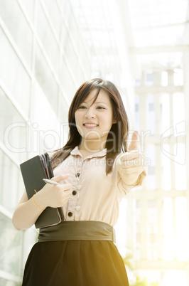 Young Asian woman thumb up