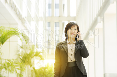 Young Asian business woman talking on phone