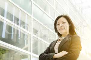 Young Asian business woman arms crossed