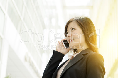 Young Asian business woman talking on mobile phone