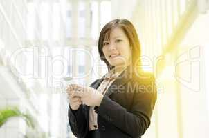Young Asian business woman texting on smartphone