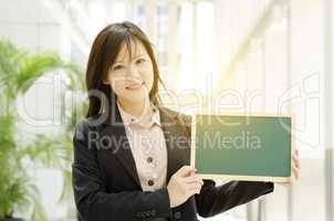 Young Asian business woman showing blank board
