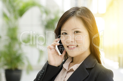 Young Asian businesswoman calling on phone
