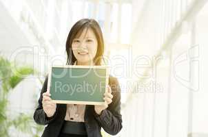 Young Asian business woman holding blank board