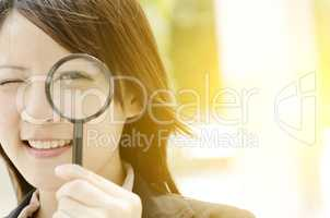 Asian female searching with magnifier