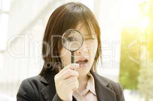Asian female looking through magnifier glass