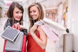 Portrait of two beautiful women shopping in mall