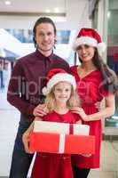 Family in Christmas attire standing with Christmas gifts