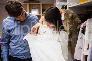 Couple selecting a dress while shopping for clothes
