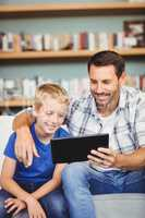 Smiling father and son using digital tablet while sitting on sof