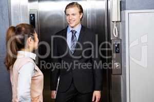 Businessman and businesswoman standing in an elevator