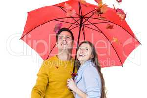 Happy couple under an umbrella throwing leaves