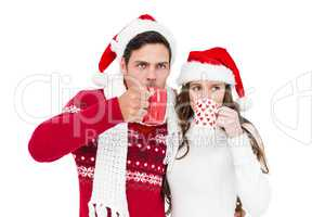 Happy couple with santa hats drinking a hot beverage