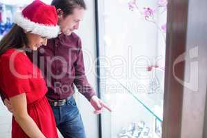 Couple in Christmas attire looking at wrist watch display