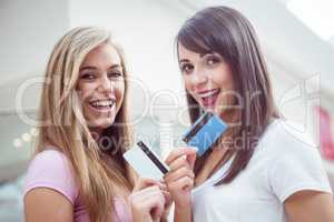 Portrait of happy women showing their credit cards in mall
