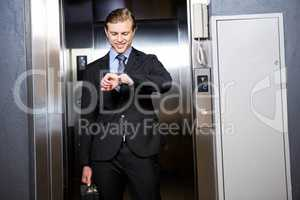 Businessman checking time in elevator