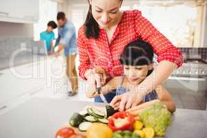 Happy mother teaching daughter to cut vegetables