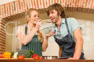 Pretty blonde making her boyfriend taste the preparation