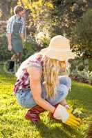 Gardener woman planting a flower with her boyfriend behind
