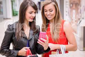 Two beautiful women looking at phone in shopping mall