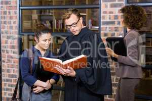 Lawyer and businesswoman reading law book