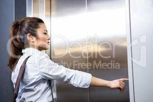 Businesswoman pressing elevator button