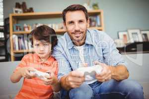 Smiling father and son playing video game