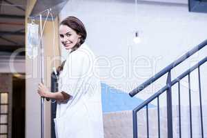Portrait of female doctor carrying saline stand