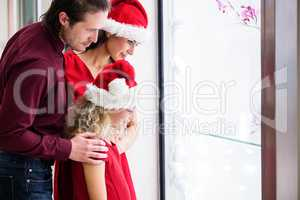 Family in Christmas attire looking at a display