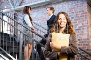 Businesswoman standing near staircase with documents