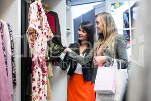 Women selecting a dress while shopping for clothes
