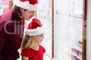 Father and daughter in Christmas attire looking at jewelry displ