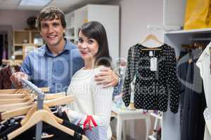 Portrait of couple selecting a dress while shopping for clothes