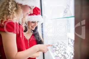 Mother and daughter in Christmas attire looking at wrist watch d