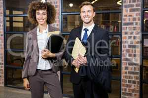 Lawyer and businesswoman standing near library with documents